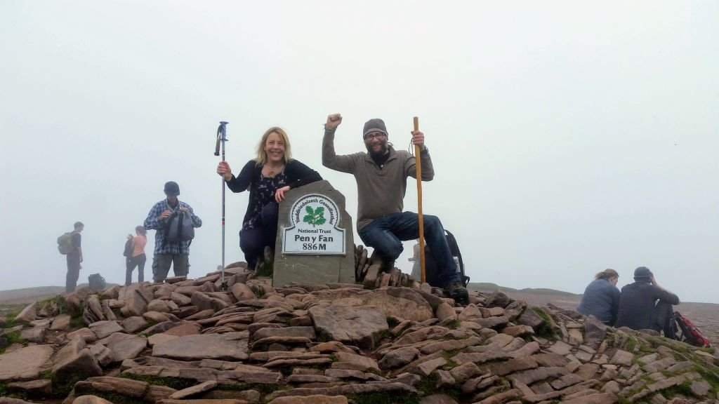 man and woman (The Motorhome Hobos!) at top of Pen Y Fan in the Brecon Beacons, Wales