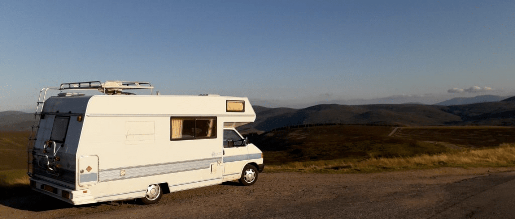 motorhome parked by roadside overlooking Cairngorms in Scotland