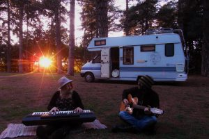 Motorhome Hobos sitting with musical instruments outside campervan